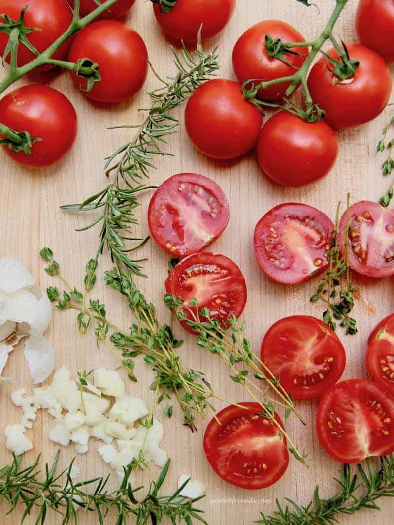 Fresh tomatoes, rosemary, oregano, and garlic on a wood cutting board.