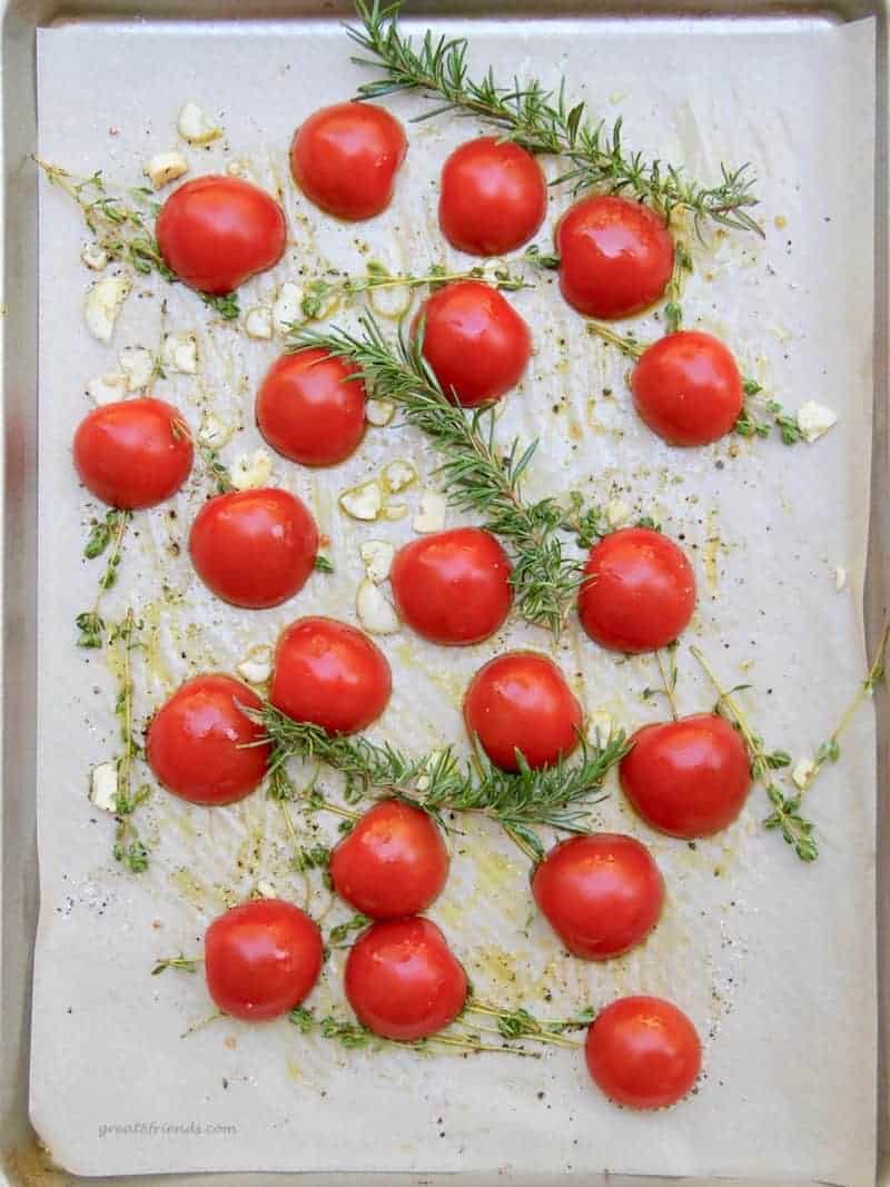 Fresh tomatoes, rosemary, thyme, and garlic on a parchment covered sheet pan ready for roasting.