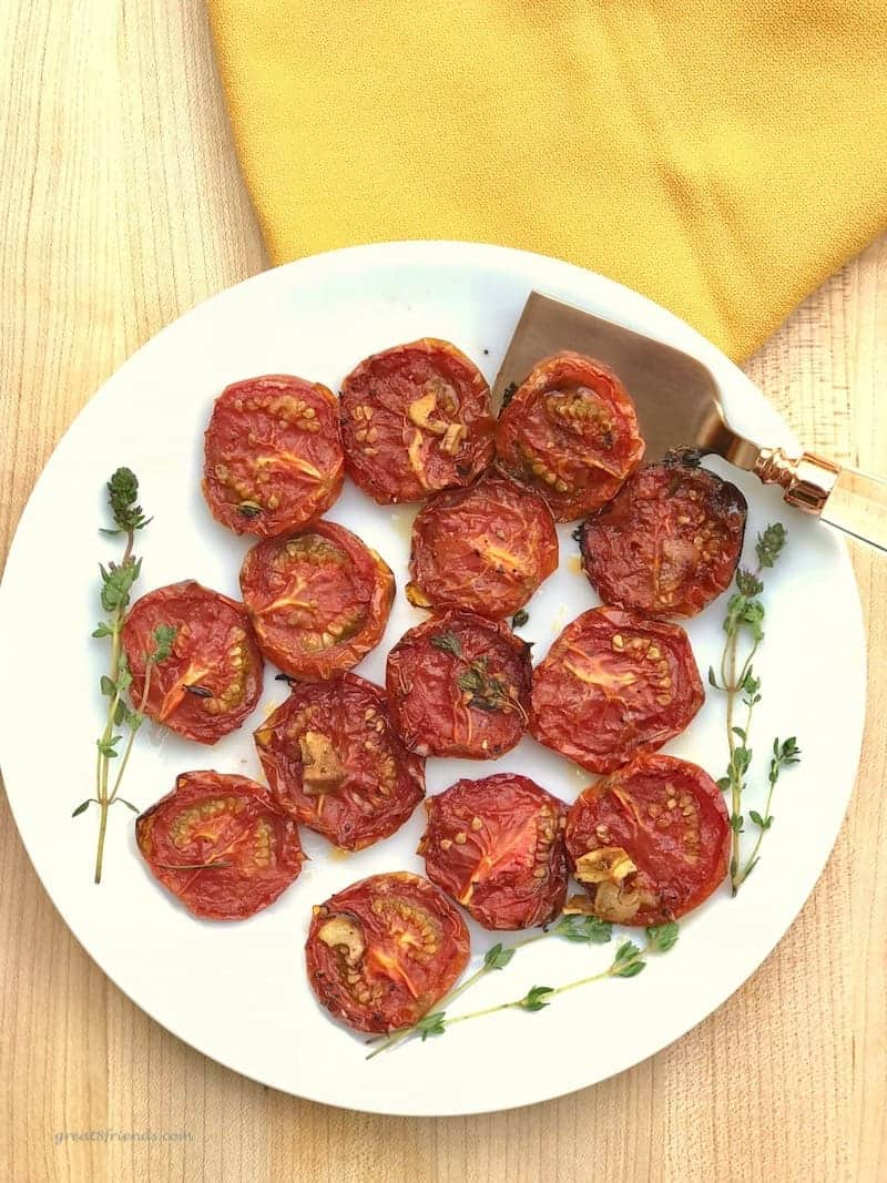 Roasted tomatoes on a plate with a serving spatula and fresh thyme.