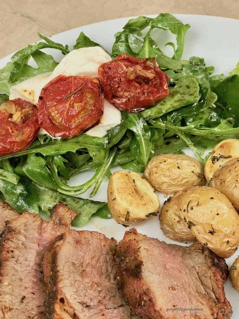 Upclose photo of roasted tomato and arugula salad on a dinner plate with roasted potatoes and slices of tri-tip roast.