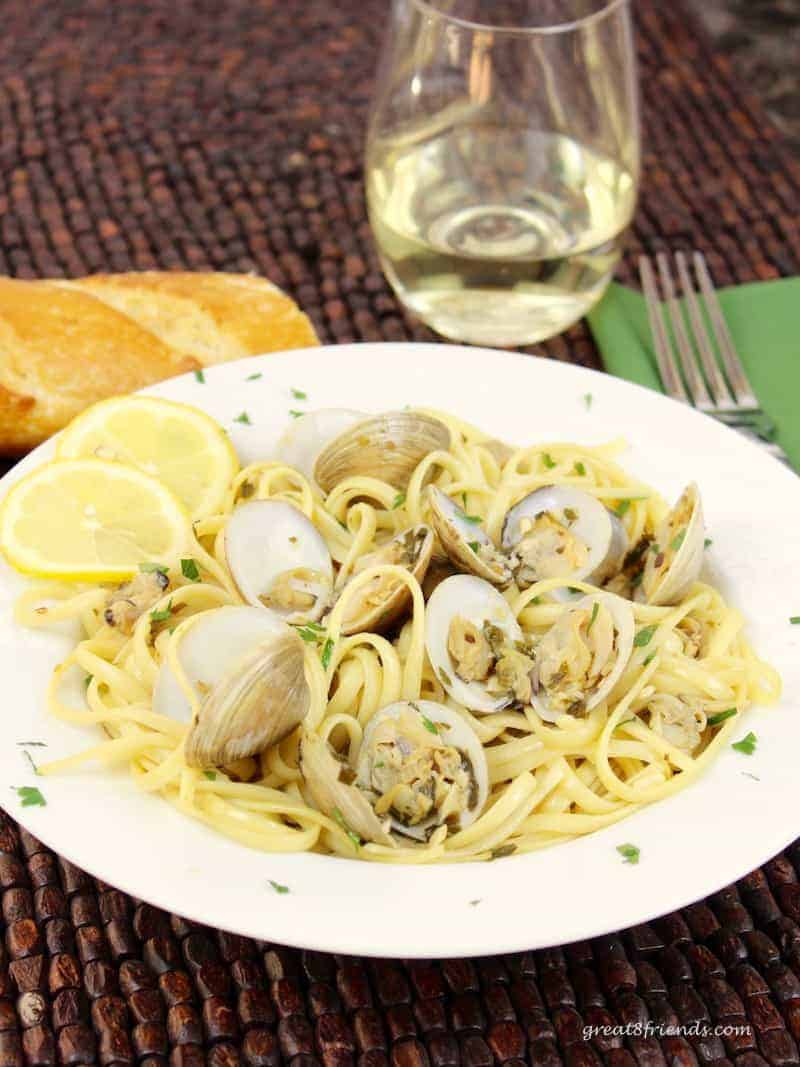 Linguine with Clams served in a white bowl with a wide brim with a glass of white wine in the background.