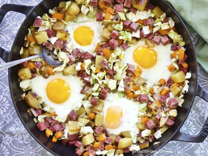 Overhead shot of corned beef hash with eggs in a cast iron skillet.