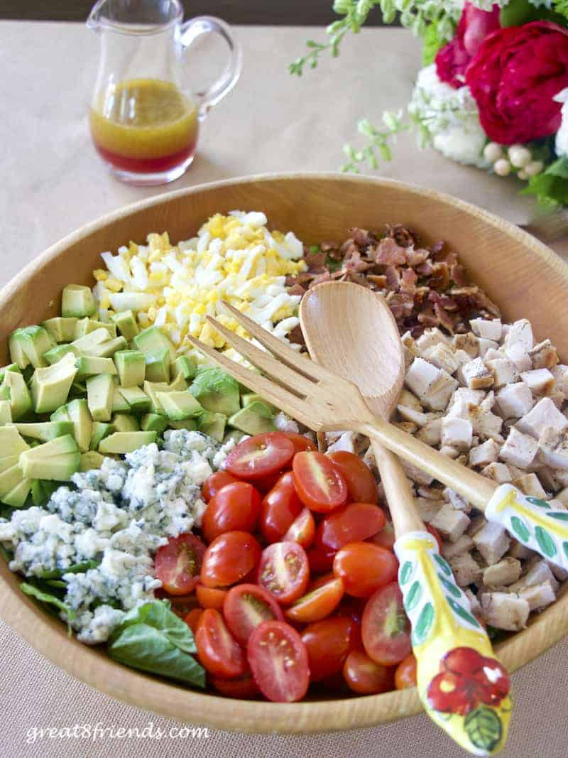 Cobb Salad with dressing in background and salad servers laying on top.