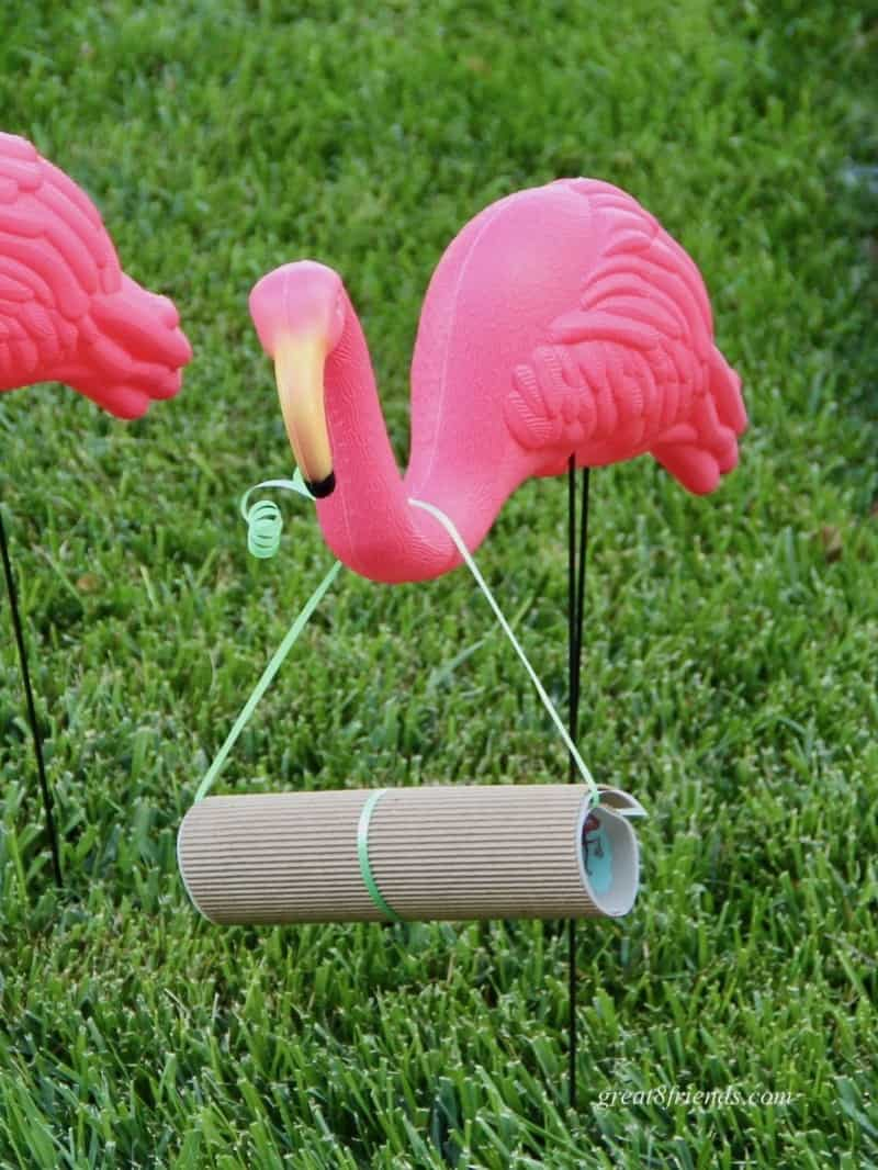 Pink plastic flamingo in grass with a scroll hanging around its neck.