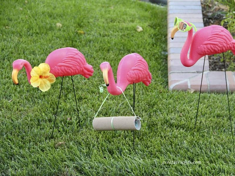 3 pink plastic flamingoes on grass one is holding a rolled up invitation to the Hot Havana in Miami dinner.