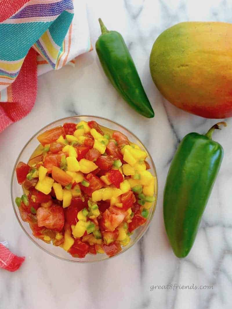 Overhead shot of Mango Papaya Salsa on marble with a couple of jalapenos and mango.