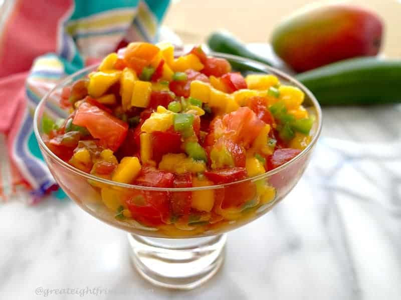 Mango Papaya Salsa in a footed glass dish on white marble.