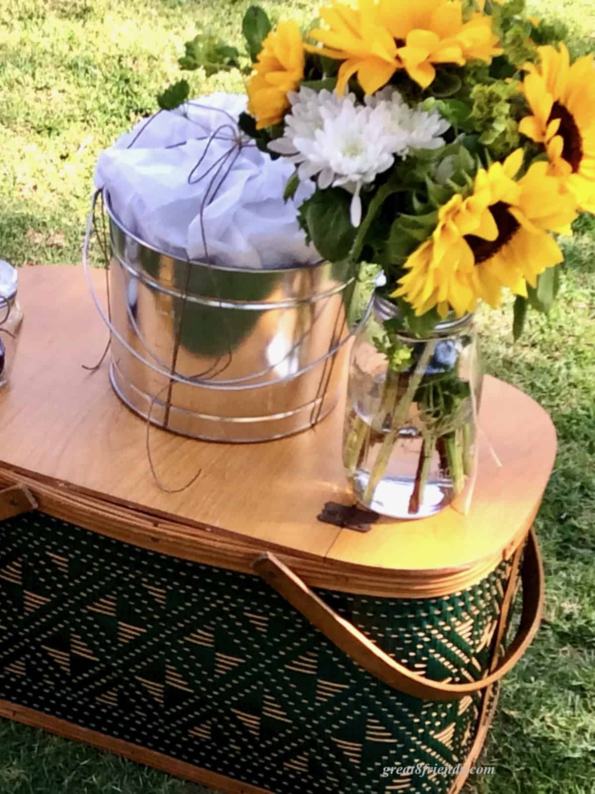 An old fashioned picnic basket with a tin buchet and vase of sunflowers on top.