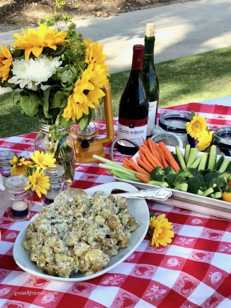 Red and White checked tablecloth set with sunflowers and picnic food.