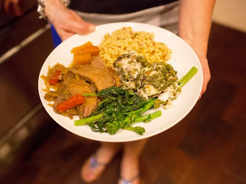 Memories from our Mother's Kitchen dinner, woman holding a white plate containing Brisket and Fried Corn and broccoli rabe.
