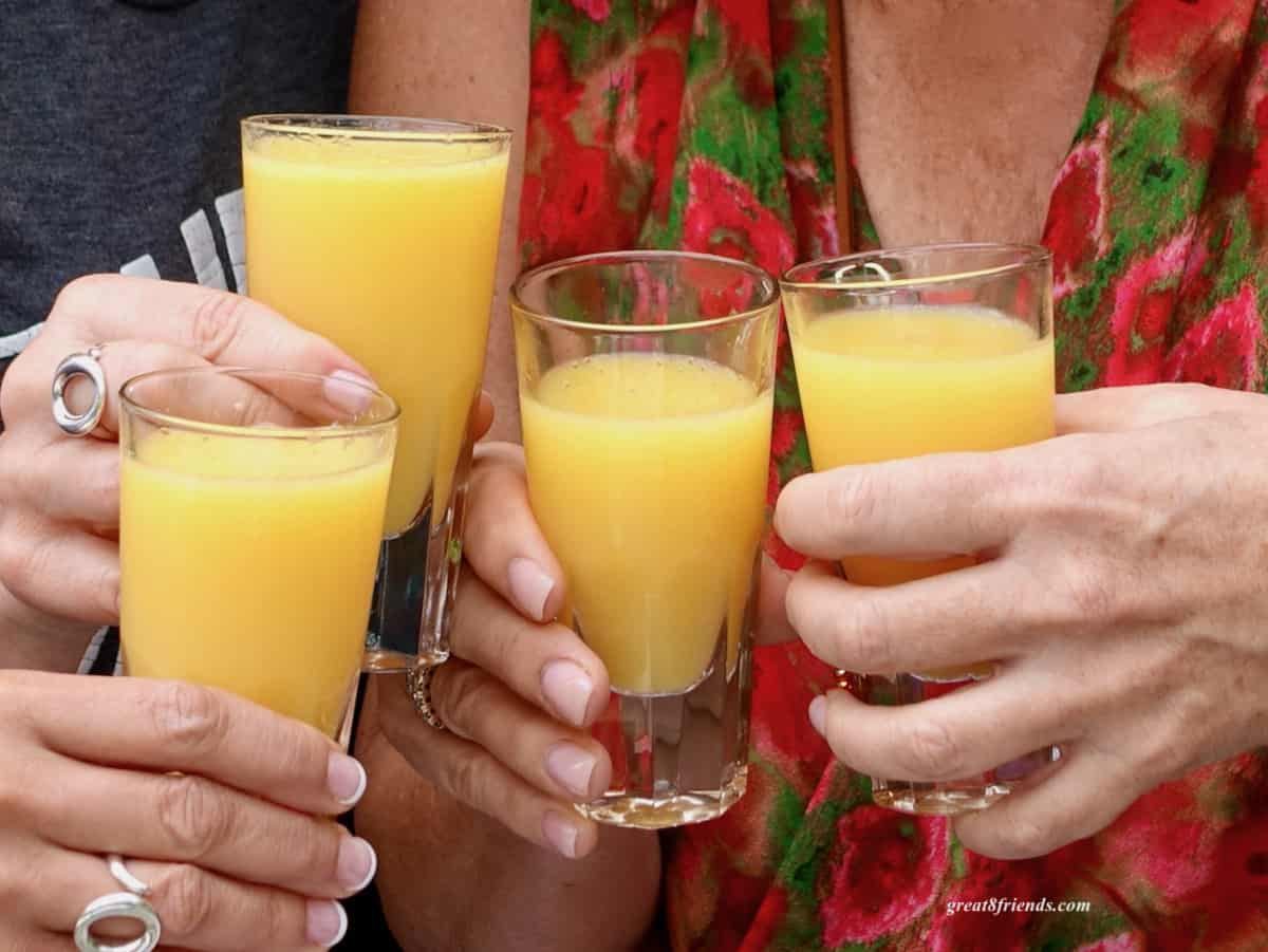 Four hands toasting glasses containing mimosas.