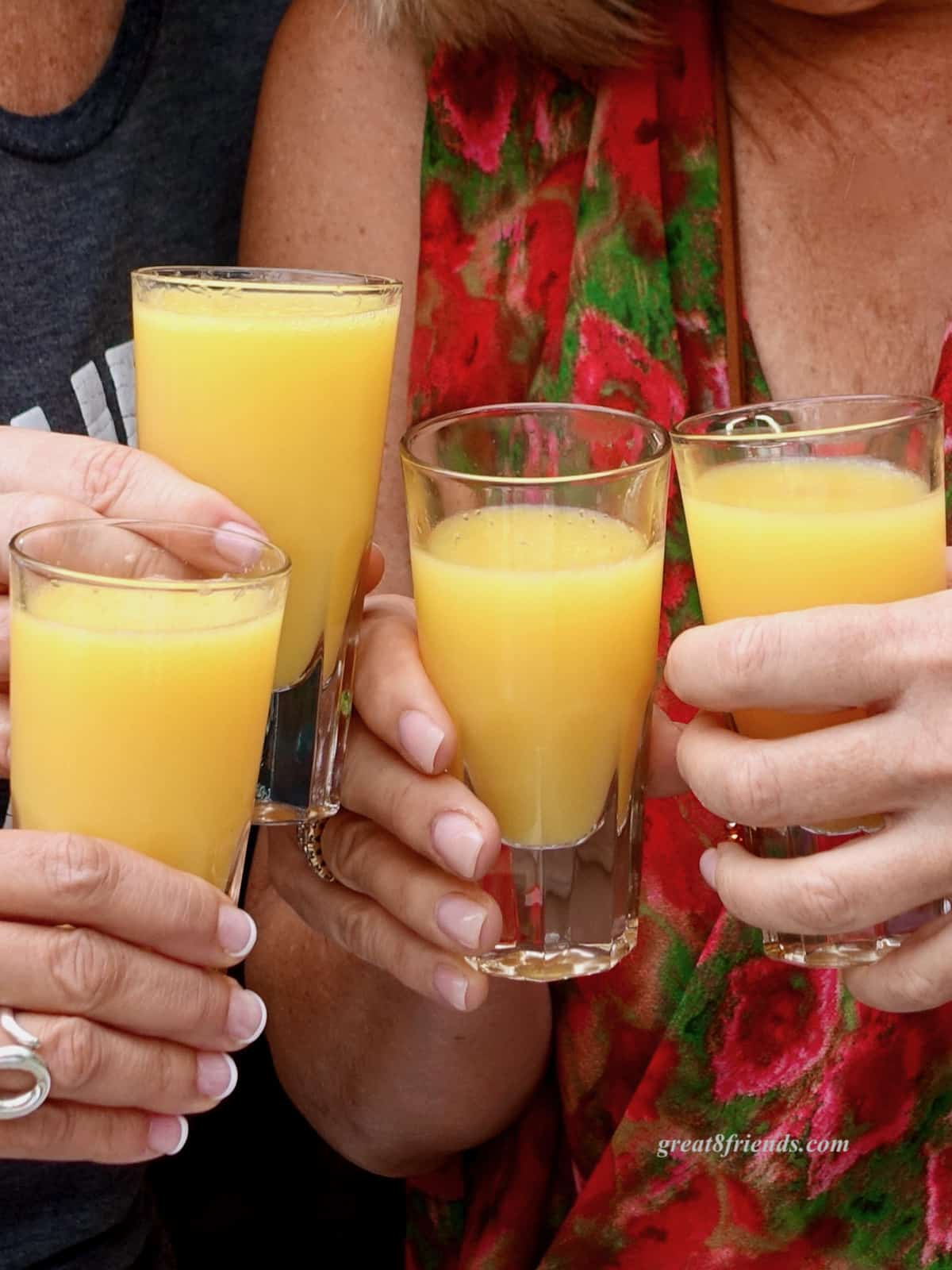 Four hands toasting glasses of mimosas.