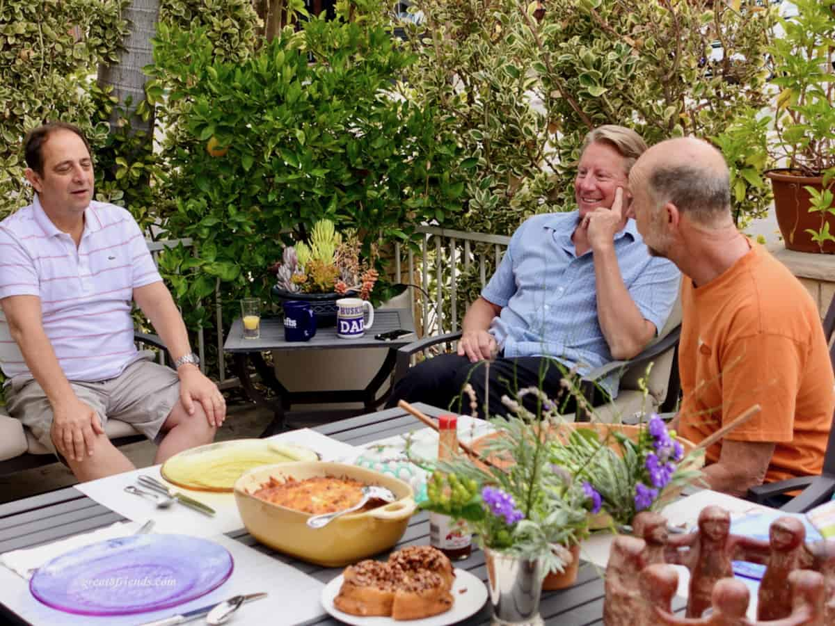 Three men sitting on a patio with a table of food in the foreground.