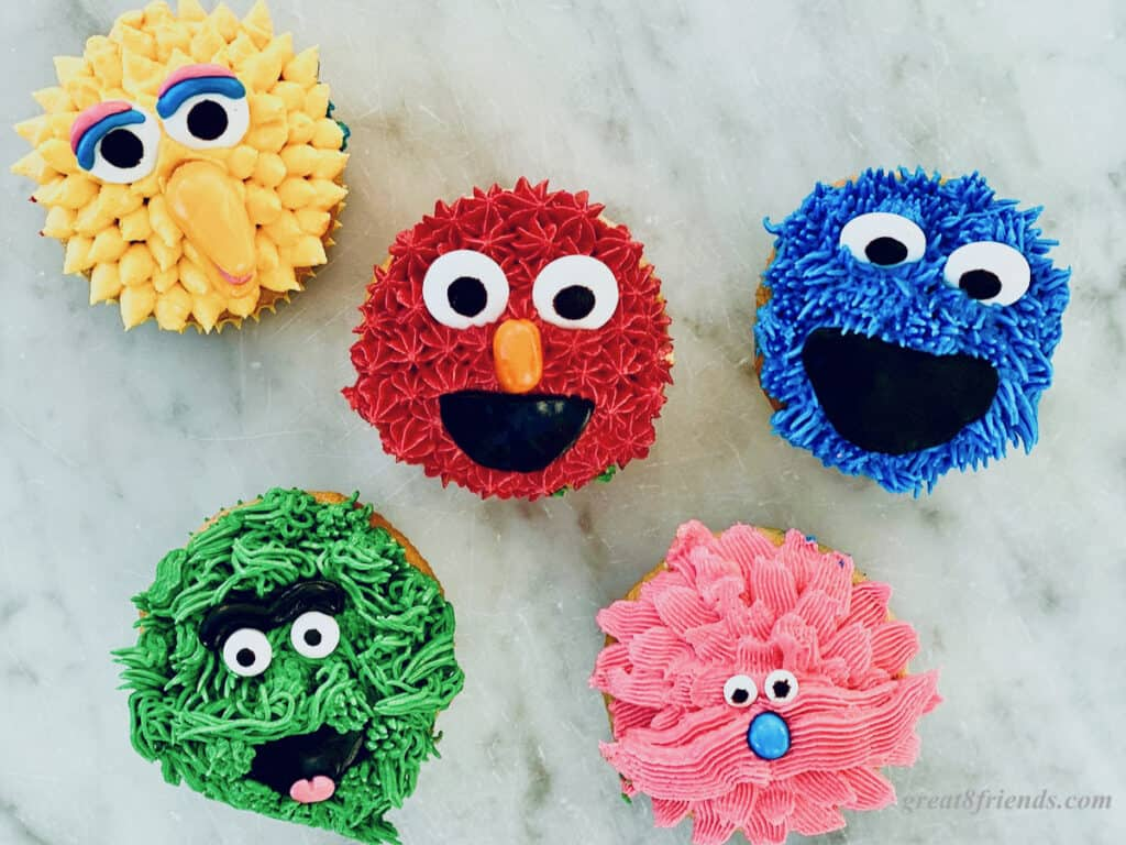 Five Sesame Street Character cupcakes, Big Bird, Elmo, Grover, Cookie Monster and a pink one.