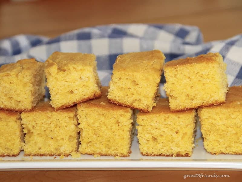 Stacked cut pieces of cornbread on rectangular platter with a blue checked cloth in the background.