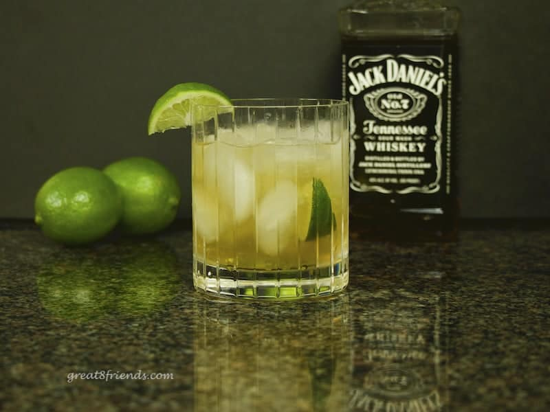 Whiskey Swirl Cocktail with Jack Daniels and limes in the background.