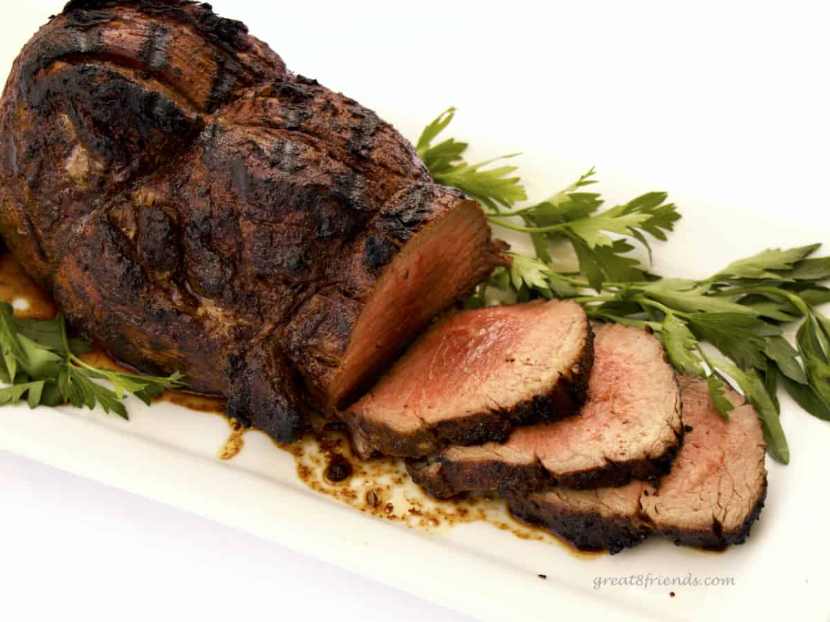 Sliced beef tenderloin roast with parsley.
