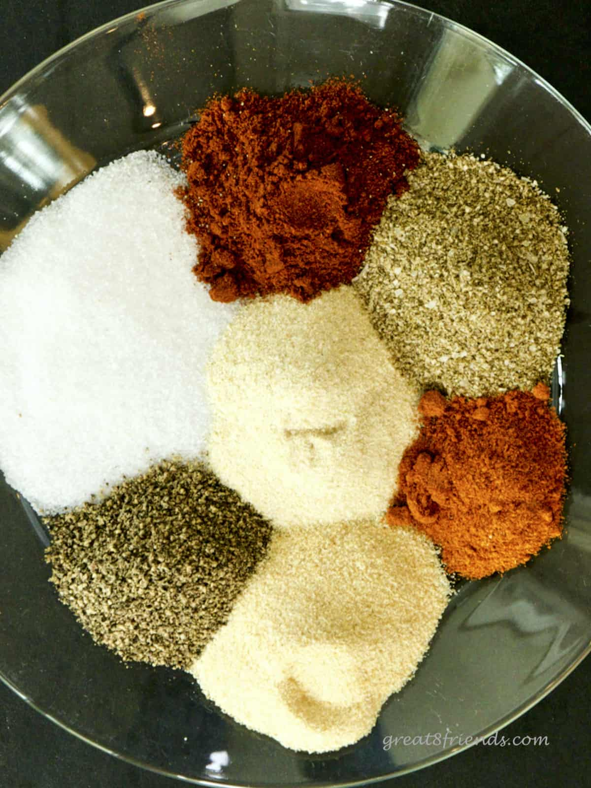 Overhead shot of 6 spices and some salt mounded on a glass plate.