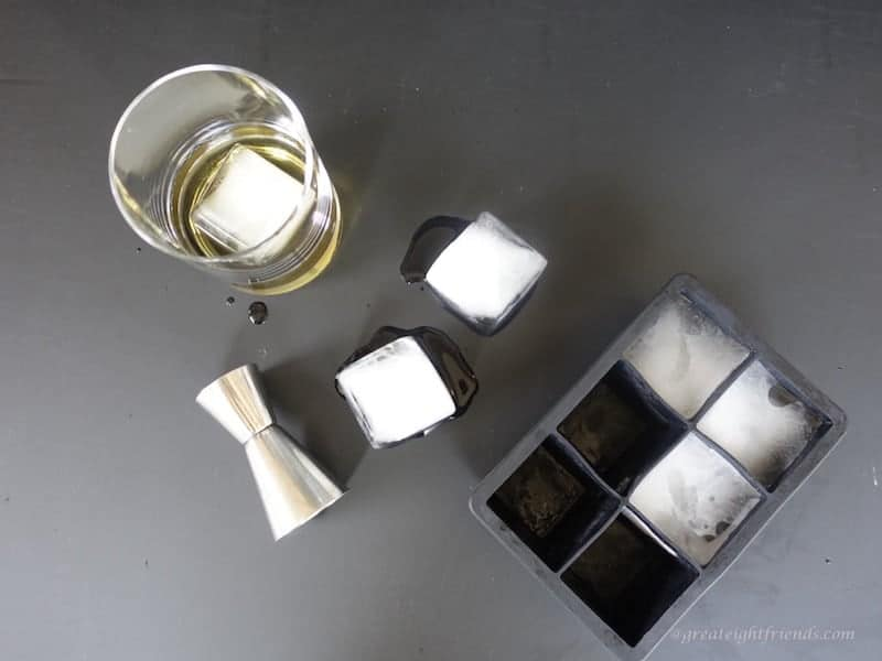Overhead shot of large ice cubes, some in black silicone cube tray and some outside. with a glass and a shot glass.