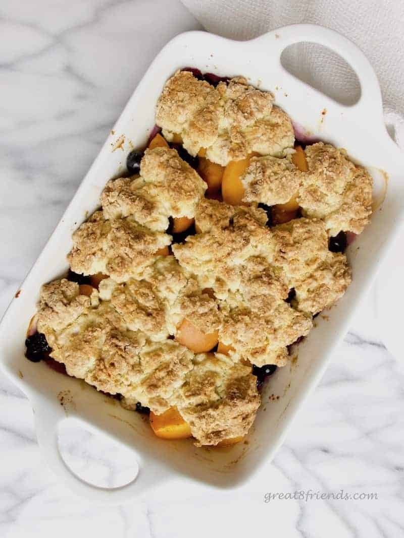 Overhead shot of Apricot Blueberry Cobbler in a white rectangular dish with handles.