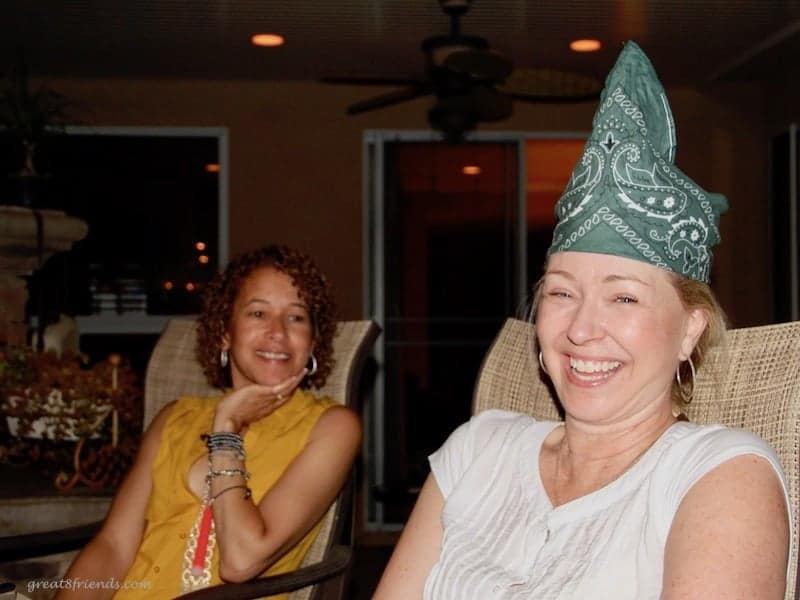 Two woman smiling while one is wearing a green bandana on her head.