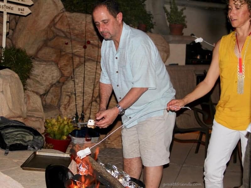 A man and a woman roasting homemade marshmallows over a fire.