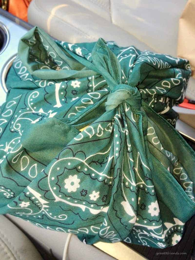A green bandana tied with the camping themed dinner party invitation inside.