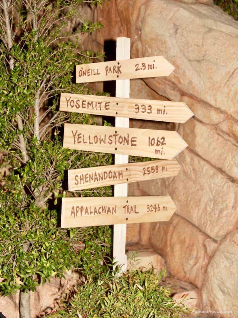A handmade wooden sign indicating direction for a camping themed dinner party.