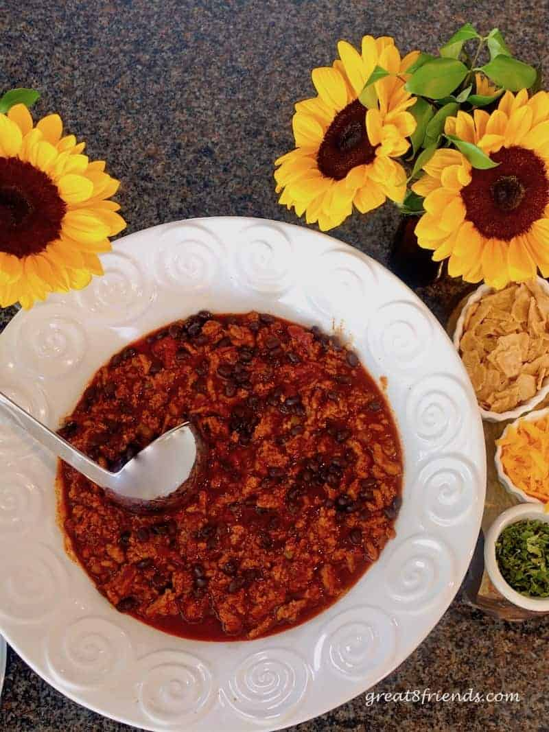 Overhead shot of turkey chili in a white serving bowl.