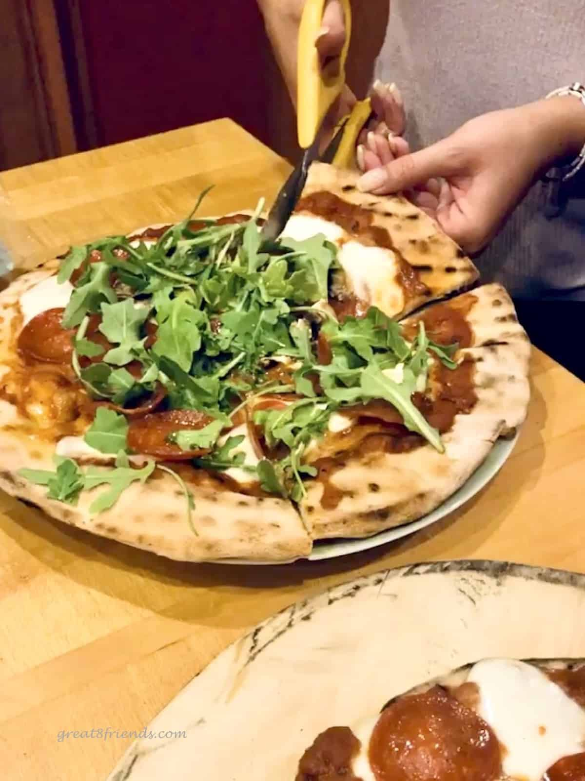 Pizza with arugula topping being cut with scissors.