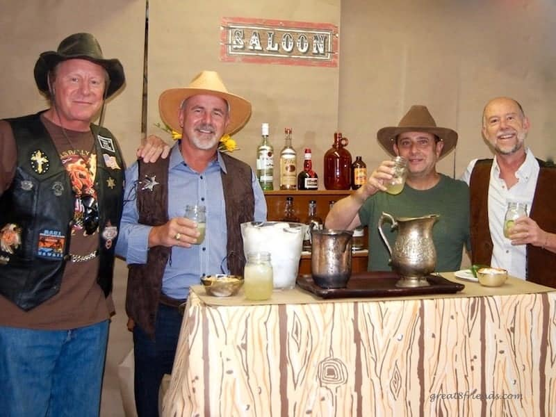 Four men in western wear standing at a bar.