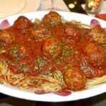 Square photo of spaghetti and meatballs.