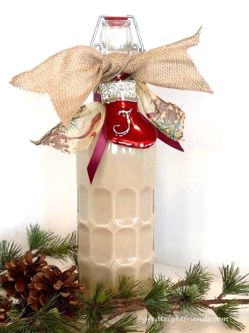 Homemade Irish Cream in a bottle decorated for Christmas with a ribbon and enamel ornament.