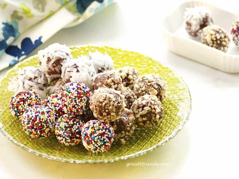 Assorted chocolate truffles on green glass plate.