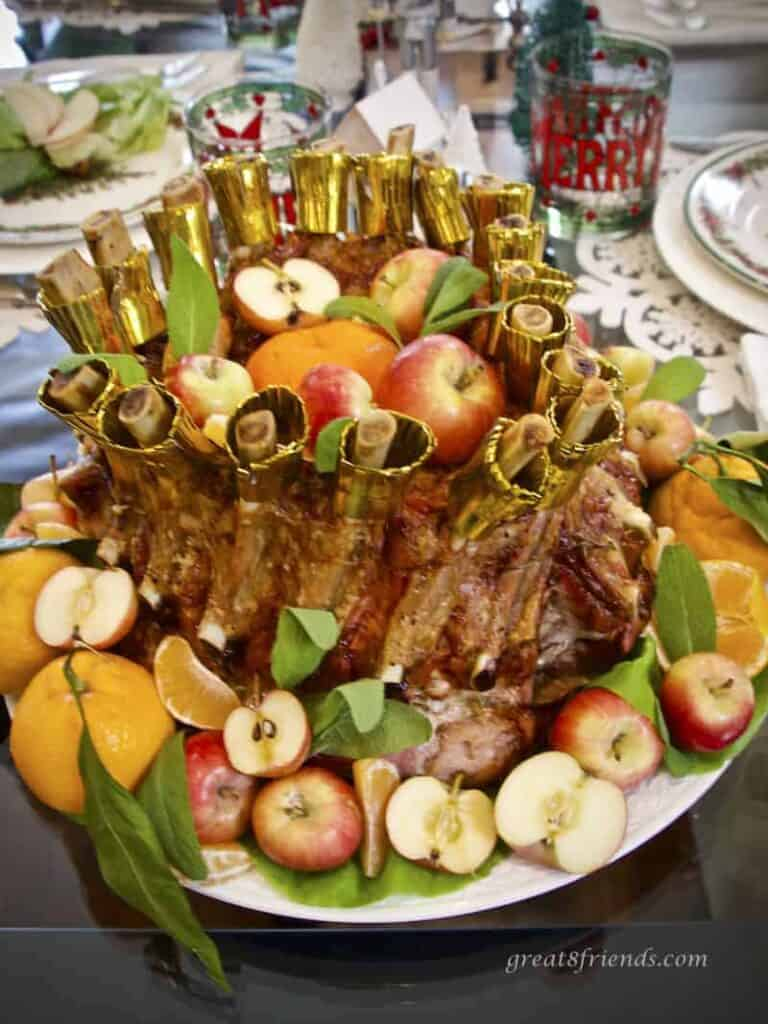 Crown Roast of Pork stuffed and surrounded with apples and tangerines, verticle photo