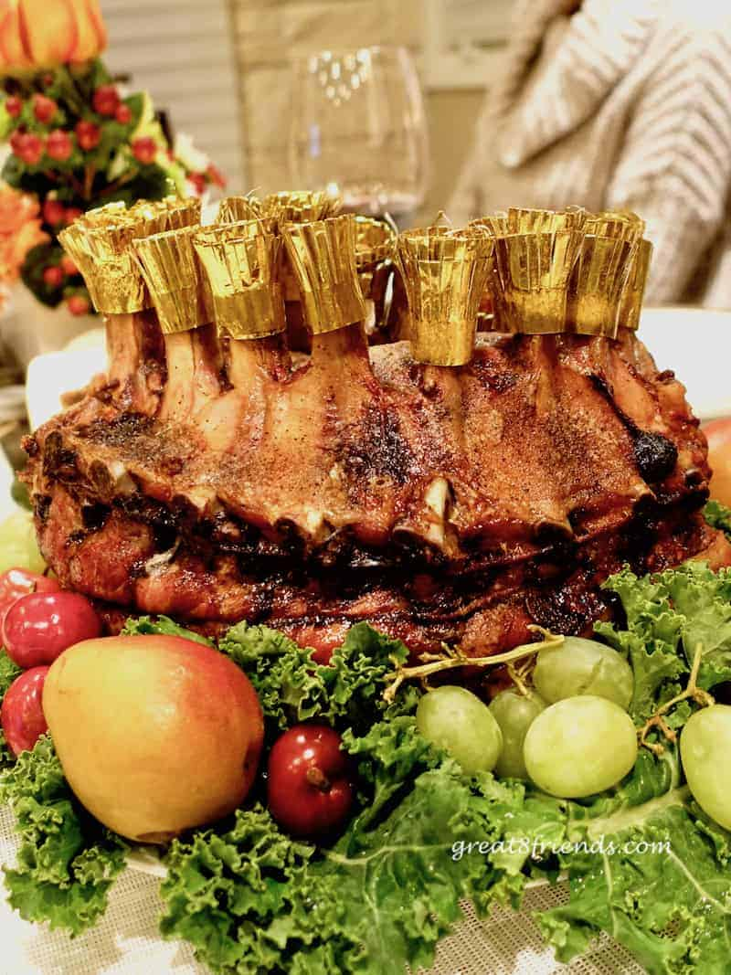 Crown Roast of Pork surrounded by fruit.