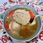 Upclose photo of a matzo ball in a spoon with the soup in a bowl below.