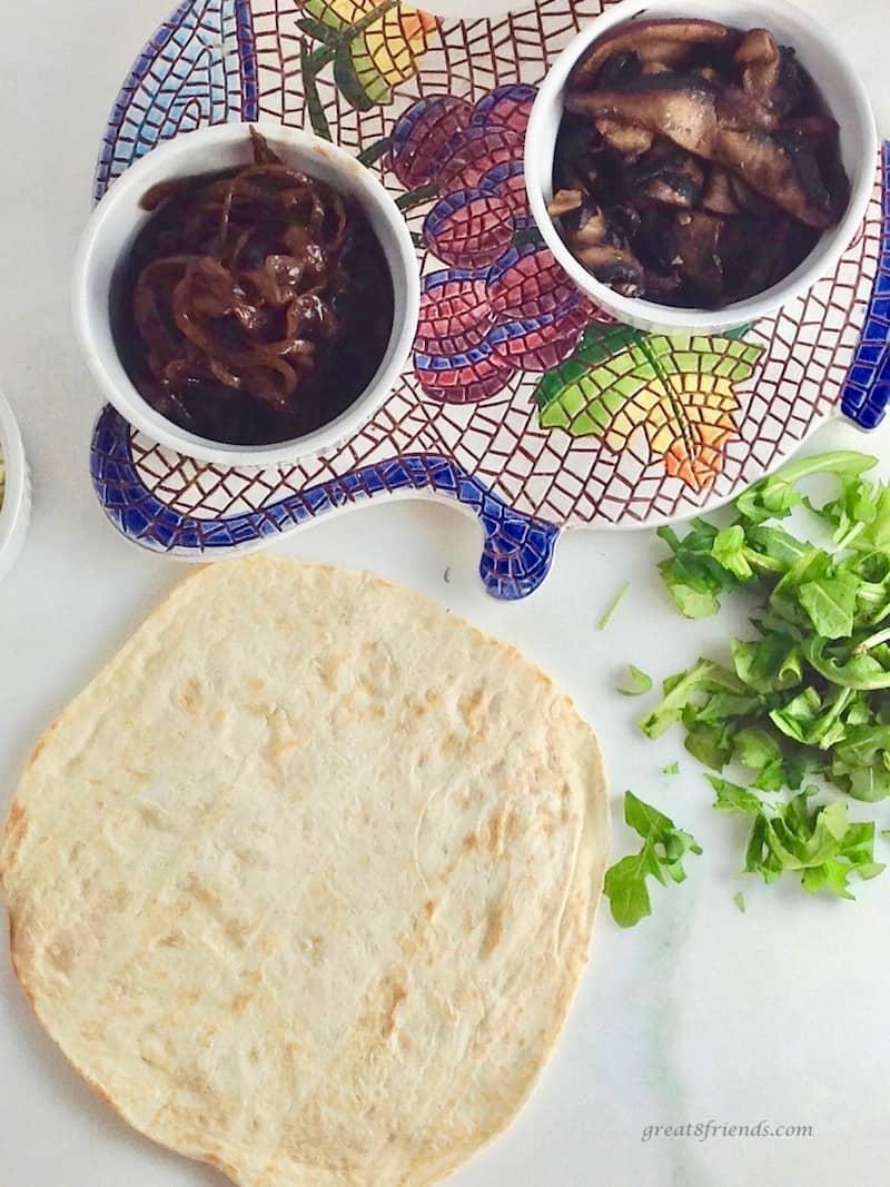overhead shot of tortillas, caramelized onions, chopped arugula and sauteed mushrooms