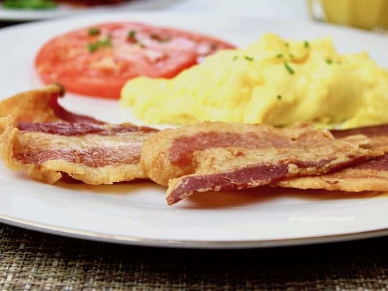 Slices of bacon, scrambled eggs and a slice of tomato on a plate.