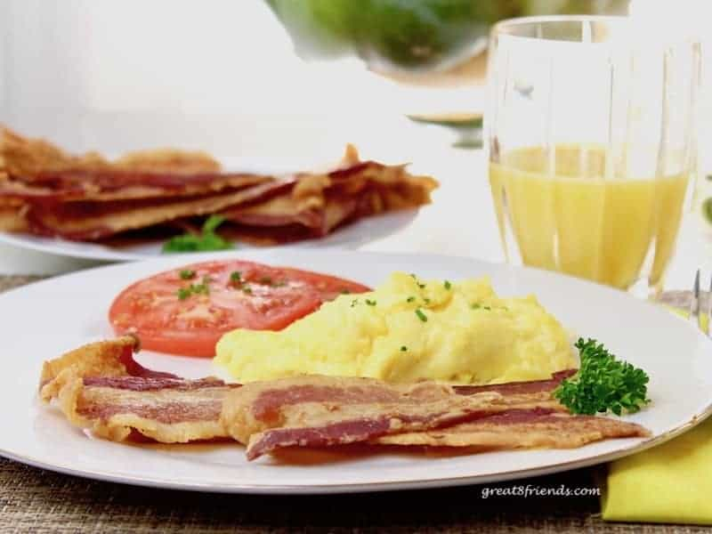 Slices of bacon, scrambled eggs and a slice of tomato on a plate with a glass of orange juice and more slices of bacon in the background.