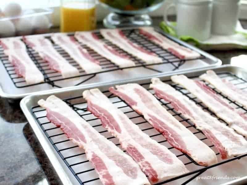 Uncooked bacon slices on two baking sheets.