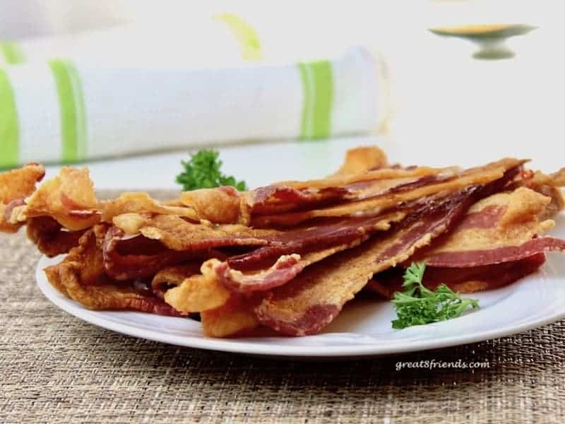 Several slices of bacon on a plate.