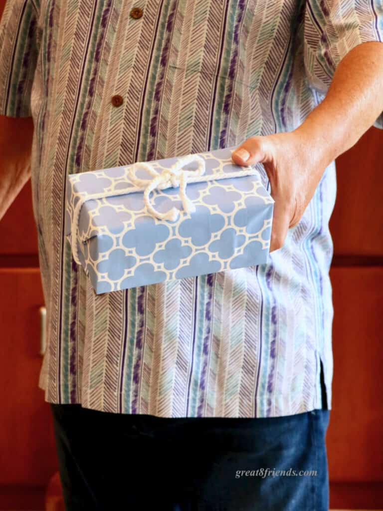 A man's hand holding a gift wrapped in blue and white paper with a white rope bow.