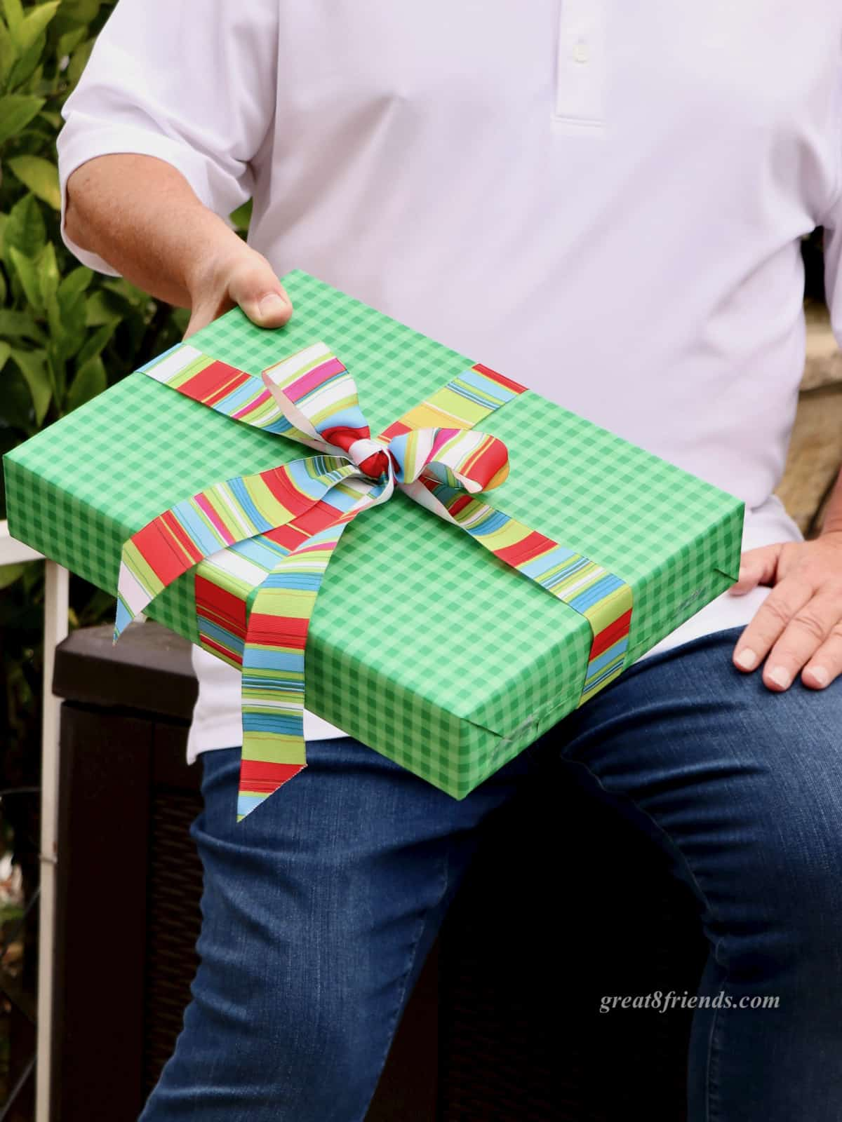 A man's hand holding a gift wrapped in green paper with a bright striped bow.