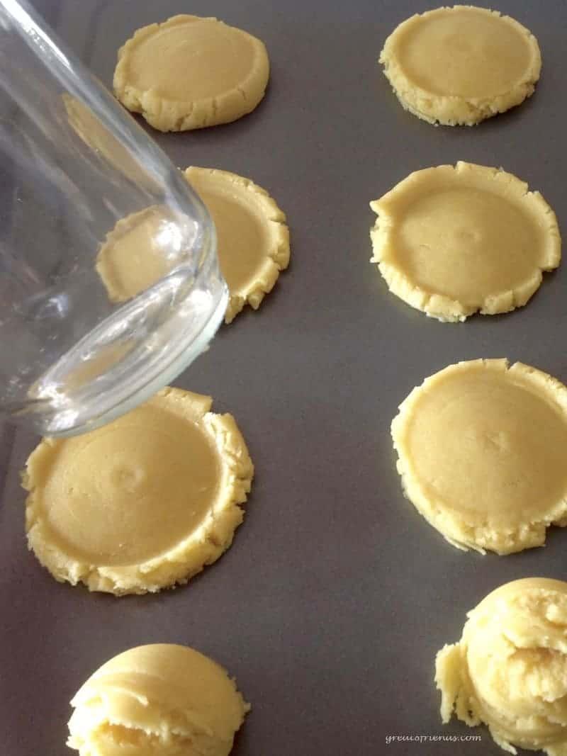 Cookie dough flattened on a baking sheet.