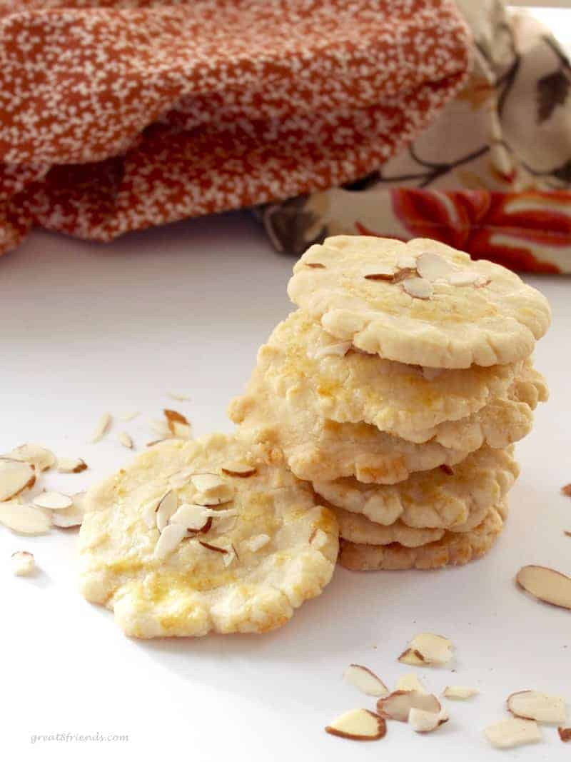 A stack of Almond Cookies with sliced almonds sprinkled around.