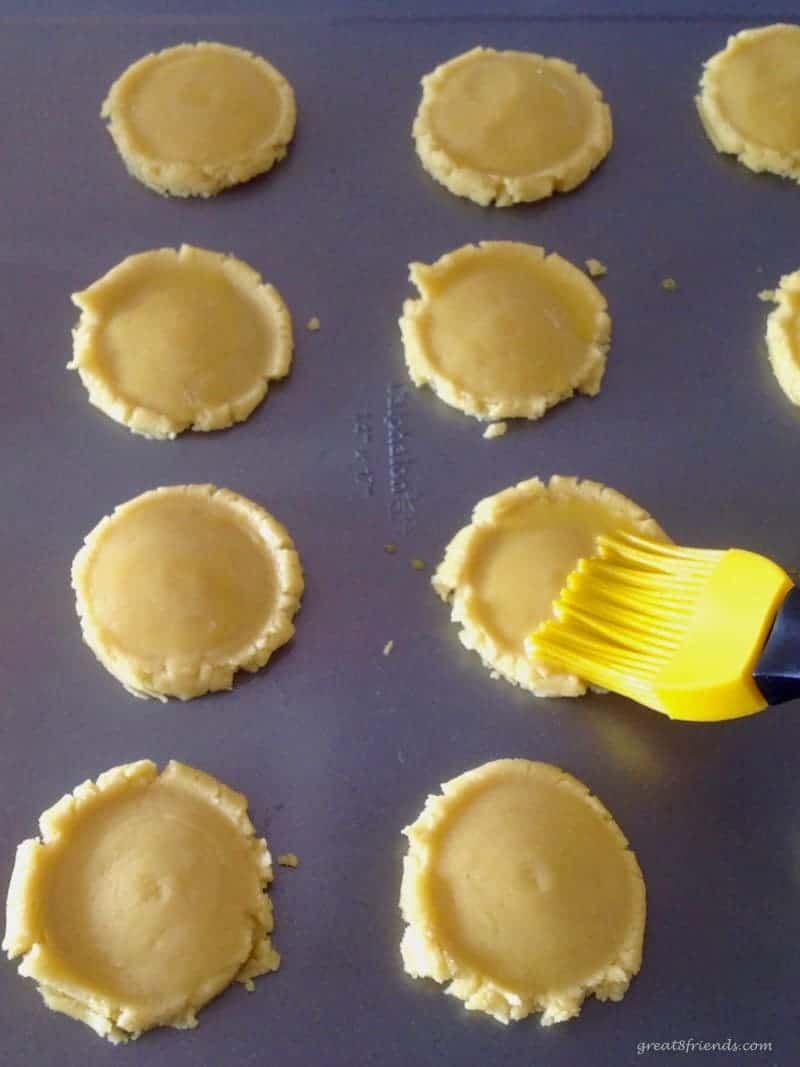 Flattened unbaked cookies being brushed with egg wash.