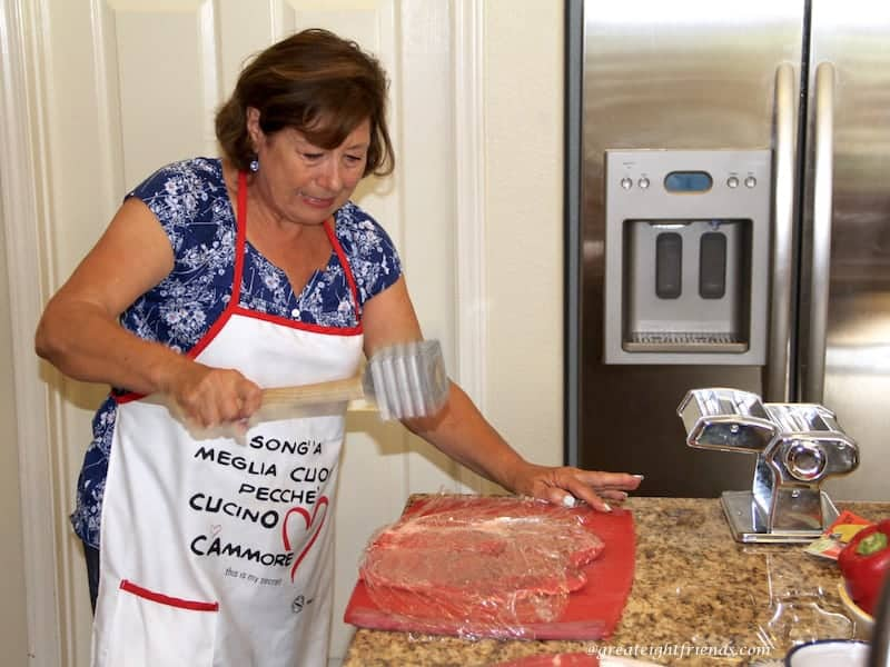 A woman pounding flank steak on a counter.