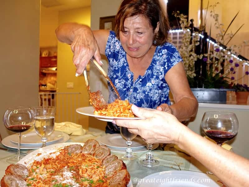 Nonna Anna filling a plate with food.