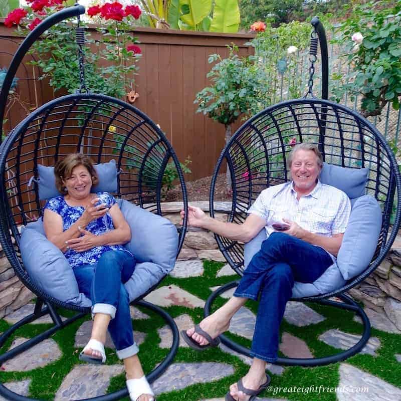 Nonna Anna and Tim relaxing in barrel chairs in the yard.